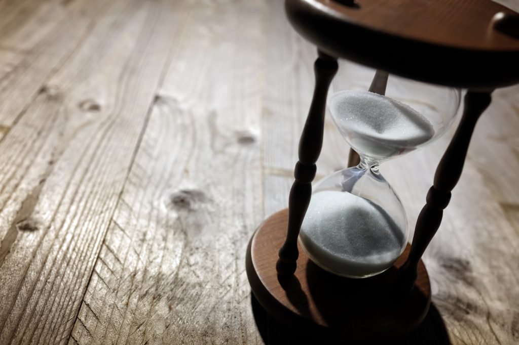 Hourglass on wooden table.