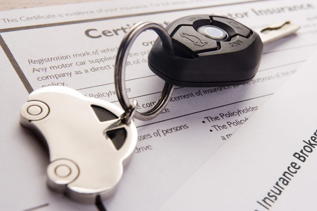 Metal car key chain with ignition key on top of an insurance certificate.
