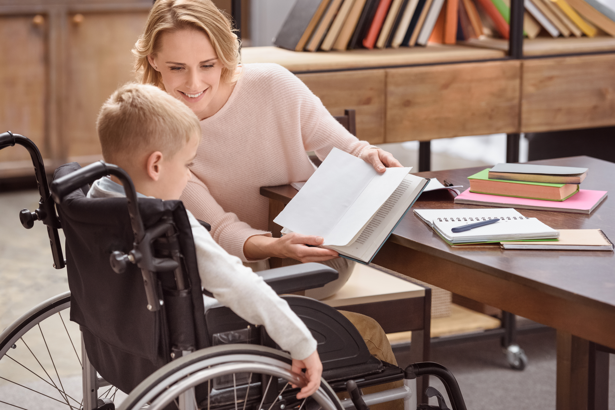 happy mom showing something in book to son in wheelchair